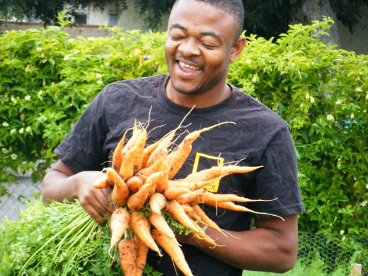 Bilali Muya cares freshly picked carrots to the sink for washing