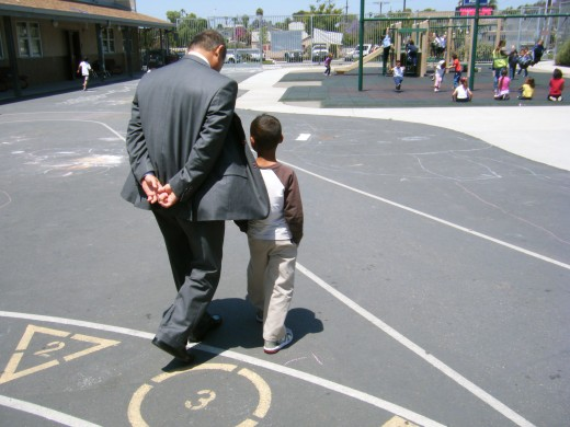 Principal Godwin Higa walks with a student on the playground